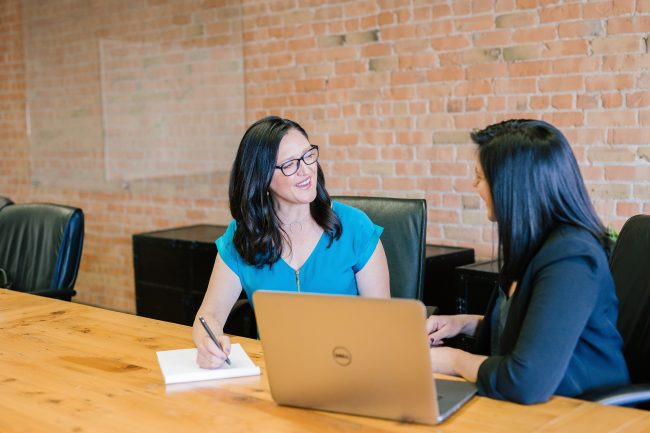 two women sitting at a desk, talking. meeting